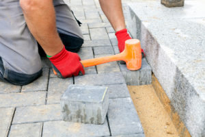 Workman installing pavers