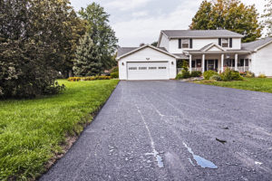 Rain puddles on new asphalt driveway