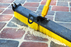 Broom moving sand between pavers